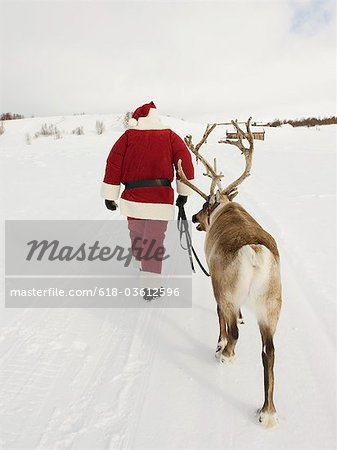 Santa Claus leading his reindeer through the snow Stock Photo - Premium Royalty-Free, Image code: 618-03612596