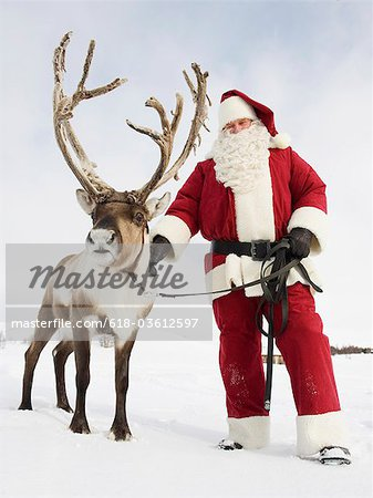 Santa Claus standing with his reindeer Stock Photo - Premium Royalty-Free, Image code: 618-03612597