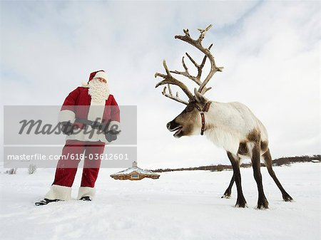 Santa Claus standing with his reindeer Stock Photo - Premium Royalty-Free, Image code: 618-03612601