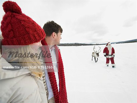 A young couple watching Santa Claus lead his reindeer through the snow Stock Photo - Premium Royalty-Free, Image code: 618-03612602