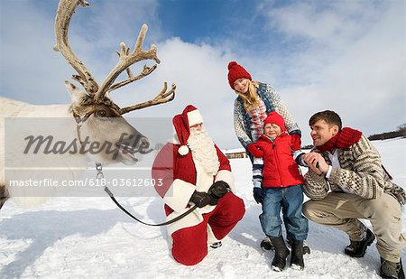 A young boy and his parents meeting Santa Claus and his reindeer Stock Photo - Premium Royalty-Free, Image code: 618-03612603