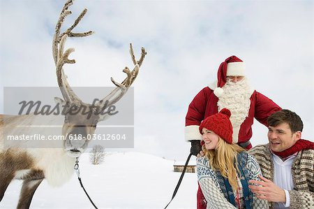 A young couple with Santa and his reindeer in the snow Stock Photo - Premium Royalty-Free, Image code: 618-03612604