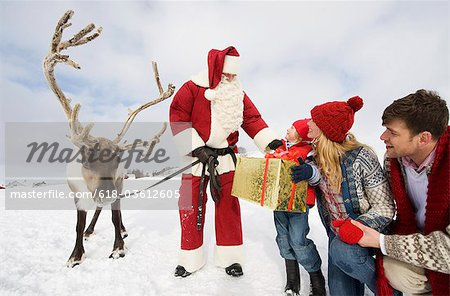 A young boy and his parents receiving a large present from Santa Claus Stock Photo - Premium Royalty-Free, Image code: 618-03612605