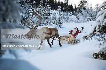 A reindeer pulling Santa Claus and his sleigh through the snow, Santa Claus waving Stock Photo - Premium Royalty-Free, Image code: 618-03612607