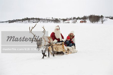 A mother and child having a sleigh ride with Santa Claus and his reindeer Stock Photo - Premium Royalty-Free, Image code: 618-03612609