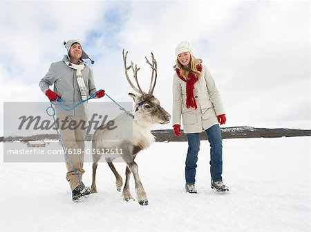 A young couple taking a baby reindeer for walk Stock Photo - Premium Royalty-Free, Image code: 618-03612611