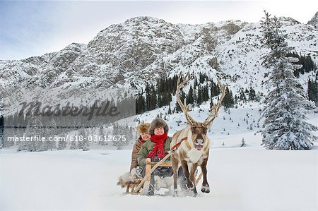 A reindeer pulling a senior couple on a sleigh Stock Photo - Premium Royalty-Free, Image code: 618-03612675
