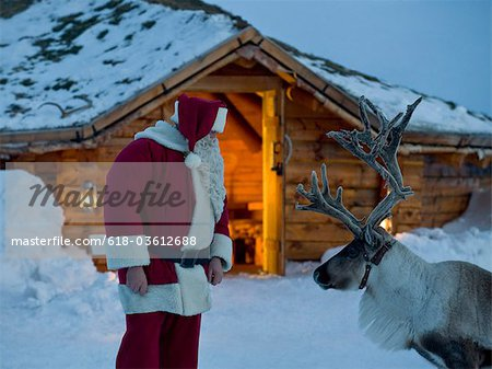 Santa Claus talking to his reindeer Stock Photo - Premium Royalty-Free, Image code: 618-03612688