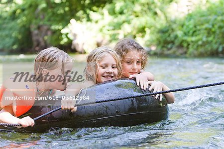 Three young girls floating down a river on an inflatable ring Stock Photo - Premium Royalty-Free, Image code: 618-03612884
