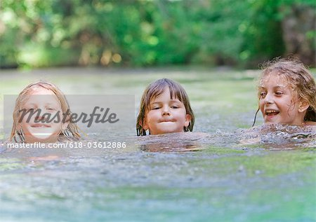 Three young girls swimming together in a river Stock Photo - Premium Royalty-Free, Image code: 618-03612886