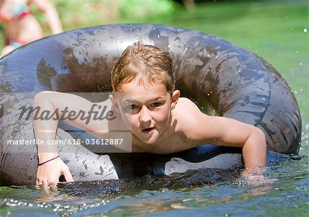 A young boy paddling in an inflatable ring Stock Photo - Premium Royalty-Free, Image code: 618-03612887