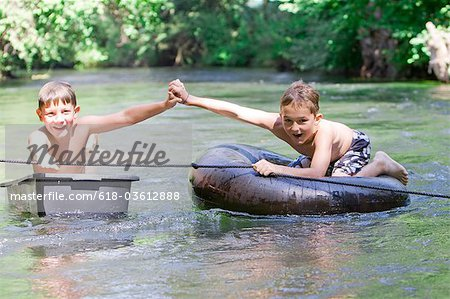Two boys floating down a river holding hands Stock Photo - Premium Royalty-Free, Image code: 618-03612888