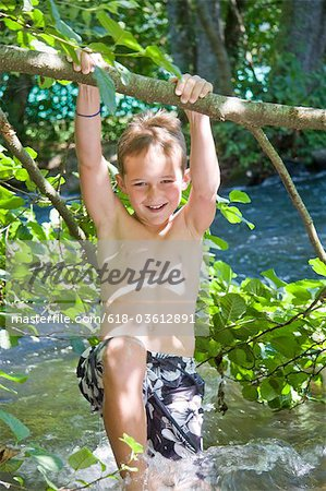 A young boy swinging from a branch over a river Stock Photo - Premium Royalty-Free, Image code: 618-03612891