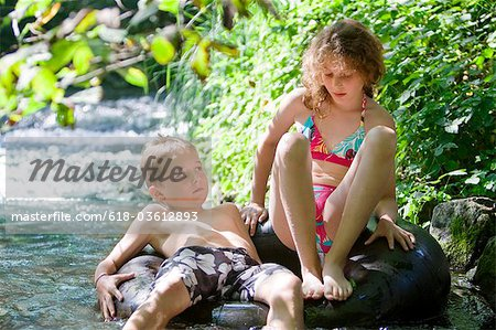 Two children floating down a river together on an inflatable ring Stock Photo - Premium Royalty-Free, Image code: 618-03612893