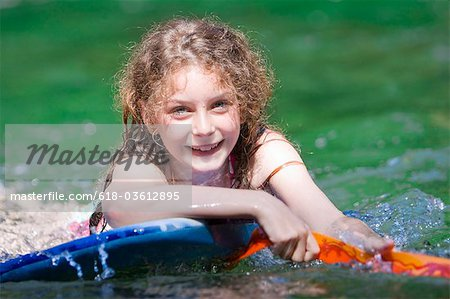 A young girl floating on a body board Stock Photo - Premium Royalty-Free, Image code: 618-03612895