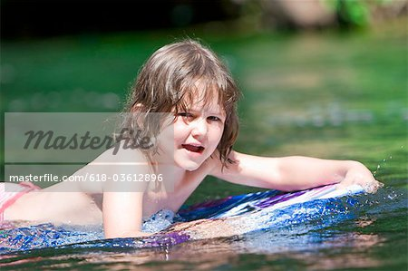 A young girl floating on a body board Stock Photo - Premium Royalty-Free, Image code: 618-03612896