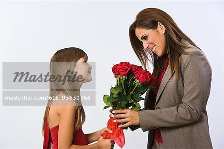 Girl (6-7) giving a bouquet of flowers to a woman Stock Photo - Premium Royalty-Free, Image code: 618-03630964