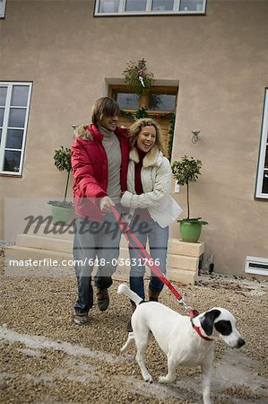 Couple walking dog on leash Stock Photo - Premium Royalty-Free, Image code: 618-03631766