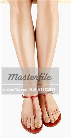Woman's legs with red sandals and fresh pedicure Stock Photo - Premium Royalty-Free, Image code: 618-03632584