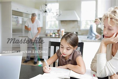 Mother helping young Girl with homework. Stock Photo - Premium Royalty-Free, Image code: 618-03632842