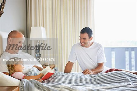Two Men reading to Young Girl in bed. Stock Photo - Premium Royalty-Free, Image code: 618-03632876