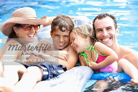 Portrait of young family in swimming pool. Stock Photo - Premium Royalty-Free, Image code: 618-03632883