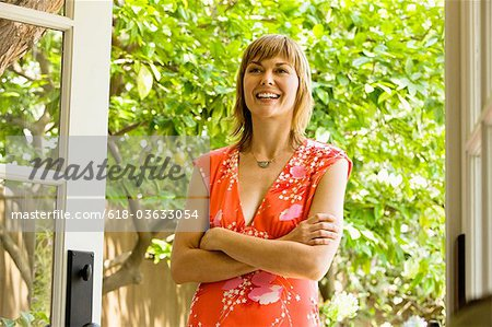 Woman in flowered dress smiling, arms crossed Stock Photo - Premium Royalty-Free, Image code: 618-03633054