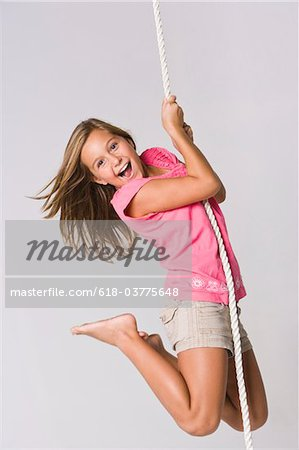 Young girl hanging from a rope, smiling, portrait Stock Photo - Premium Royalty-Free, Image code: 618-03775648