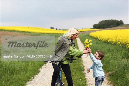 Young boy giving mother on bicycle yellow flowers Stock Photo - Premium Royalty-Free, Image code: 618-03780449