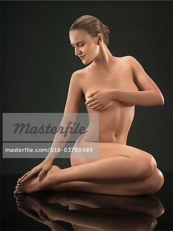 Portrait of young nude woman sitting and posing, studio shot Stock Photo - Premium Royalty-Free, Image code: 618-03780489