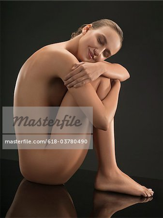 Portrait of young nude woman sitting and hugging herself, studio shot Stock Photo - Premium Royalty-Free, Image code: 618-03780490