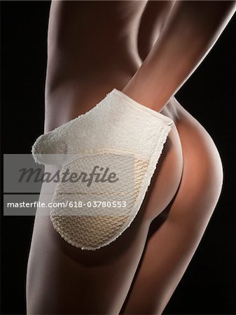 Close-up of young nude woman wearing oven mitt, studio shot Stock Photo - Premium Royalty-Free, Image code: 618-03780553