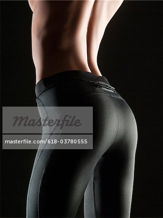 Close-up of topless young woman wearing black stretch pants, studio shot Stock Photo - Premium Royalty-Free, Image code: 618-03780555