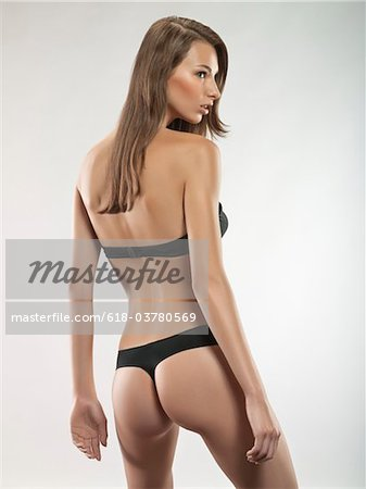 Portrait of young sexy woman in thong and bra, studio shot Stock Photo - Premium Royalty-Free, Image code: 618-03780569