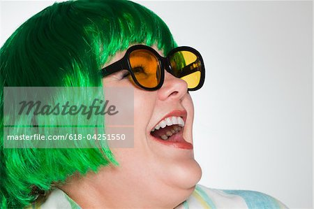 Woman with green wig and sunglasses laughing Stock Photo - Premium Royalty-Free, Image code: 618-04251550
