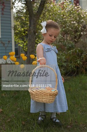 Three yeasr old girl with Easter basket in Dress Stock Photo - Premium Royalty-Free, Image code: 618-05551175