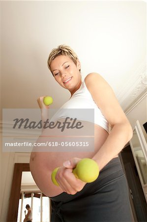 Pregnant woman lifting weights Stock Photo - Premium Royalty-Free, Image code: 618-05605315