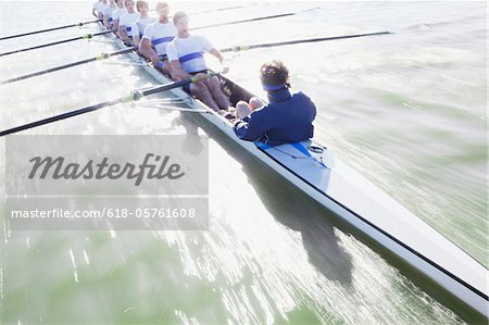 Men sitting in a line oaring canoe Stock Photo - Premium Royalty-Free, Image code: 618-05761608