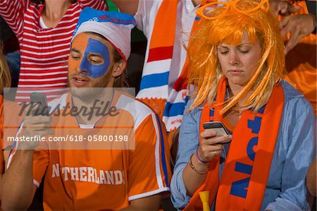 Dutch fans looking at phone at soccer game in Cape Town, South Africa Stock Photo - Premium Royalty-Free, Image code: 618-05800198
