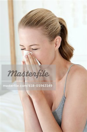Woman Sneezing Into Tissue Stock Photo - Premium Royalty-Free, Image code: 618-05963149