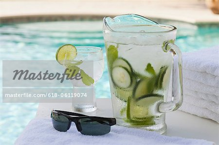 Pitcher and glass of water with cucumber by pool Stock Photo - Premium Royalty-Free, Image code: 618-06119074