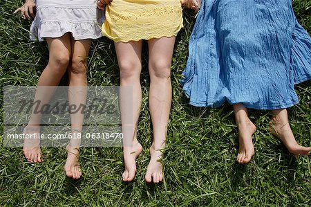 Cropped shot of legs of three teen girls lying on the grass Stock Photo - Premium Royalty-Free, Image code: 618-06318470
