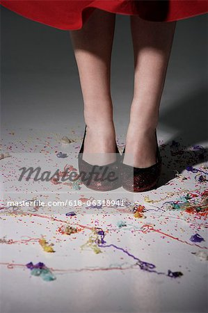 close up of woman wearing red shoes with confetti on the floor Stock Photo - Premium Royalty-Free, Image code: 618-06318941