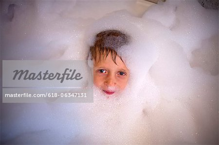 A young boy inside a bubble bath smiling Stock Photo - Premium Royalty-Free, Image code: 618-06347131