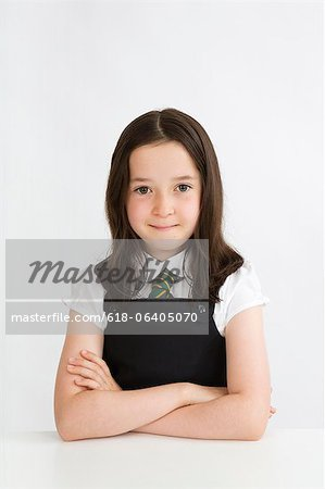 Young school girl sitting at desk Stock Photo - Premium Royalty-Free, Image code: 618-06405070
