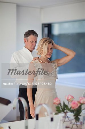 Mature man adjusting necklace of woman in mirror Stock Photo - Premium Royalty-Free, Image code: 618-06405482