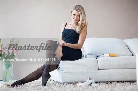 Mature woman sitting on sofa in black dress and stockings, portrait Stock Photo - Premium Royalty-Free, Image code: 618-06405495