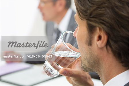 Businessman sipping water in meeting, close up Stock Photo - Premium Royalty-Free, Image code: 618-06405563