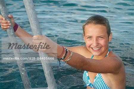 Girl climbing out of sea, portrait Stock Photo - Premium Royalty-Free, Image code: 618-06405666