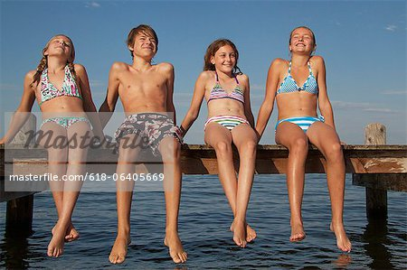 Young friends sitting in a row on pier Stock Photo - Premium Royalty-Free, Image code: 618-06405669